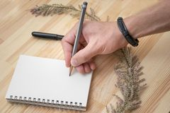 Photo of drawing in notepad male hand with bracelet stock photo