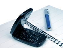Office time. Mobile phone and ball-pen on a spiral notebook-over white Stock Photos