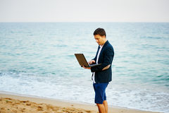 From the office to the sea . Young man businessman running into the sea with a laptop Stock Photography