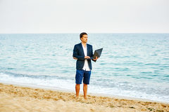 From the office to the sea . Young man businessman running into the sea with a laptop Royalty Free Stock Photos