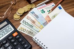 Office tools with empty notebook and euro bills. On wooden table Stock Photo