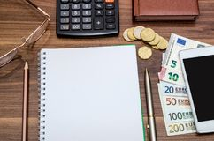 Office tools with empty notebook and euro bills. On wooden table Stock Photos