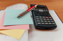 Office tools. Red pen, colored notes, calculator and an opened diary, office concept Royalty Free Stock Photography