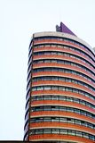 Office tower. Curved office building with brick cover against blue sky royalty free stock images