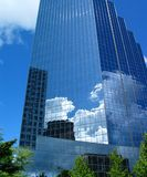 Office Tower. Reflective blue office tower with nearby buildings and clouds stock image