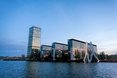 Office towers at sunset on a river, with large sculpture nearby - Berlin royalty free stock photography