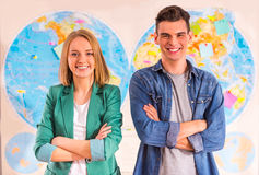 Office Travel Agency. Portrait of a young men and women chooses a place to travel through area, sitting in office travel agency Stock Photos