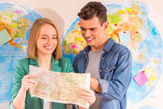 Office Travel Agency. Portrait of a young men and women chooses a place to travel through area, sitting in office travel agency Royalty Free Stock Photos
