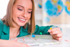 Office Travel Agency. Portrait of a young woman chooses a place to travel using map sitting in office travel agency Stock Photo