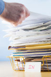 Office In Tray with Hand. Business image of a male hand with blue shirt cuff visible, adding or removing document from tall pile in overflowing office In tray royalty free stock photo
