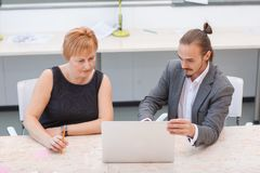 In the office, two employees are looking at the laptop. Royalty Free Stock Photography