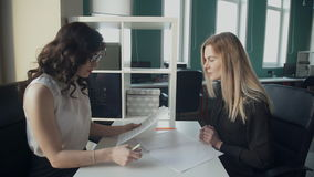 In the office, two women at the desk exchange important documents. Blonde signs the contract handle and stretches of beautiful brunette with long curly hair stock video footage