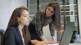 In office two women discuss working question in front of laptop. Head in stylish glasses and female subordinate talk and in front of monitor stock footage