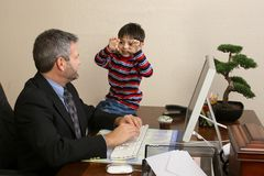 Office Visit. Office working talking to small child sitting on desk Stock Photo