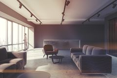 Waiting room, brown armchairs, reception toned. Office waiting room interior with loft windows, a concrete floor and brown and gray armchairs standing next to Royalty Free Stock Photography