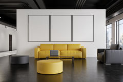 Office waiting room: sofa, gallery, front. Office waiting room interior with a yellow sofa, a gray armchair, a poster gallery on a white wall and a narrow table Royalty Free Stock Image