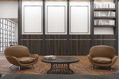 Office waiting room with two comfortable dark leather armchairs near a round coffee table. There is a bookcase and three vertical posters. 3d rendering. Mock Royalty Free Stock Images
