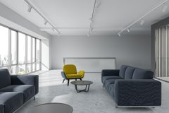 Office waiting room, yellow armchairs, reception. Office waiting room interior with loft windows, a concrete floor and yellow and blue armchairs standing next to Stock Photo