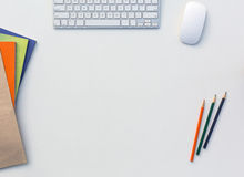 Office White Table with Computer Keyboard Mouse Color Pencils Booklets and other Supplies Royalty Free Stock Photo