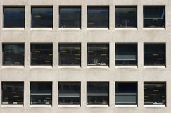 Office Windows. Eighteen square office windows each showing interior lights on during the day Royalty Free Stock Photo