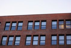 Office windows on a brick building. Patterns of office windows on a brick building Royalty Free Stock Photo