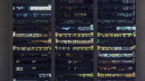 Office windows on facade of a modern skyscraper showing business activity. Office glowing windows on facade of a modern skyscraper showing business activity on stock video footage