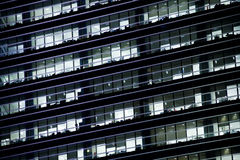 Office windows in the night. Office windows after the sunset. Some people are still working Royalty Free Stock Photography