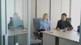 In office woman answers questions of business man at an interview. An employee of large company listens to an emotional story from female applicant for new job stock video footage