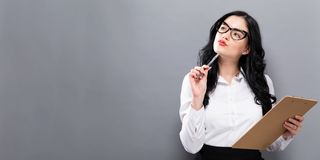 Office woman with a clipboard. On a solid background Stock Photography