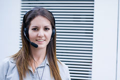 Office woman with headset phone. Call center pretty woman answering headset phone Stock Image