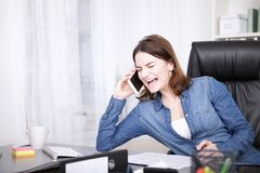 Office Woman Laughing While Talking on the Phone Royalty Free Stock Photo