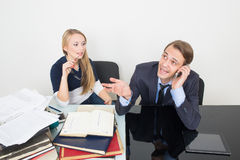 Office. woman looking for information in books. Office. Girl with books. The men speaks on the phone Royalty Free Stock Photo