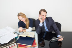 Office. woman looking for information in books. Office. Girl with books. The men speaks on the phone Royalty Free Stock Photography