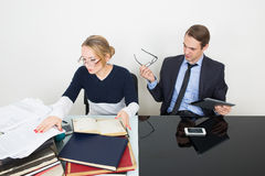 Office. woman looking for information in books. Office. Girl with books. The men speaks on the phone Royalty Free Stock Image