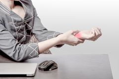 Carpal tunnel syndrome at left wrist. Office woman pain at right wrist, case woman woking at table and pain at right wrist because of hard work, office syndrome royalty free stock photography