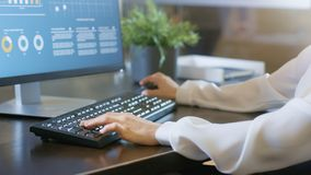 In the Office Woman`s Hands Typing on Keyboard, Monitor Showing stock images