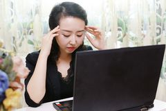 A fatigued Asian office woman. Office woman at work look tired. The look of a headache royalty free stock images