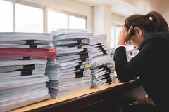 Office woman worker is distressed with a lot of paperwork on her desk. Office woman worker is distressed with a lot of paperwork on her desk royalty free stock images
