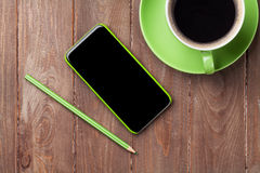 Office wooden desk with smartphone and coffee Royalty Free Stock Image