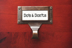 Office Wooden File Cabinet with Dos and Donts Labe stock images