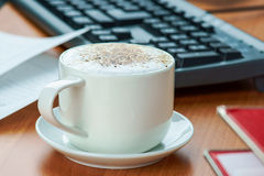Office wooden table with coffee cup and work essential tools Stock Image