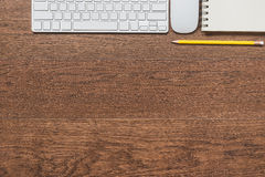 Office wooden table with notebook, yellow pencil, keyboard, and Stock Image