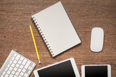 Office wooden table with notebook, yellow pencil, tablet, keyboa. Rd, mouse and smartphone, top view Royalty Free Stock Image