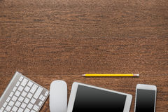 Office wooden table with notebook, yellow pencil, tablet, keyboa. Rd, mouse and smartphone, top view Royalty Free Stock Photos