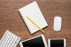 Office wooden table with notebook, yellow pencil, tablet, keyboa. Rd, mouse and smartphone, top view Royalty Free Stock Images
