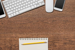 Office wooden table with notebook, yellow pencil, tablet, keyboa. Rd, mouse and smartphone, top view Royalty Free Stock Photo