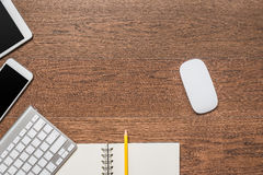 Office wooden table with notebook, yellow pencil, tablet, keyboa. Rd, mouse and smartphone, top view Royalty Free Stock Photography