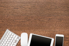 Office wooden table with tablet, keyboard, mouse and smartphone Royalty Free Stock Photos