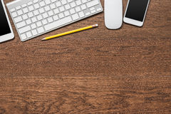 Office wooden table with yellow pencil, tablet, keyboard, mouse Stock Photography