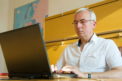 Office work. Casual businessman with glasses working on laptop royalty free stock images
